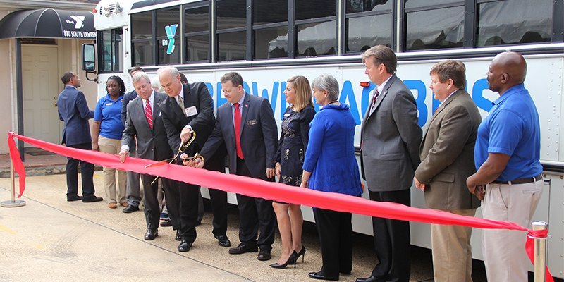 YMCA of Greater Montgomery Teams Up With Coca-Cola To End Hunger With Brown Bag Bus Food Truck. Men and Women cut the red tape on the Food Truck the YMCA of Greater Montgomery will use to help end hunger with their Brown Bag Bus.