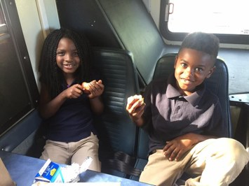BBB. Brown Bag Bus. YMCA Montgomery Brown Bag Bus.. BBB 2 kids eating. Image of two african american children eating a lunch inside the brown bag bus.